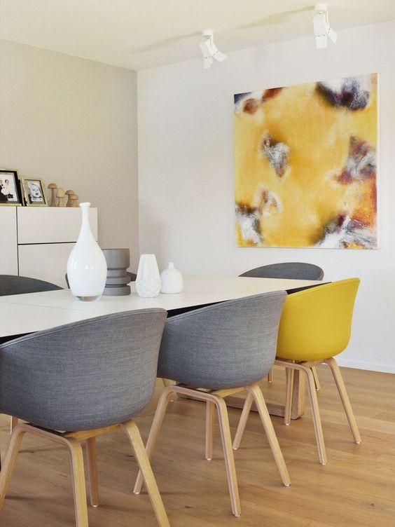 une salle à manger contemporaine avec des murs neutres, un meuble de rangement, une table blanche, des chaises grises et jaunes et une œuvre d'art assortie