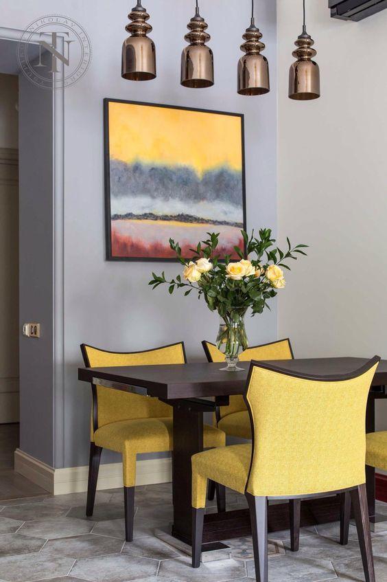 un espace salle à manger chic et lumineux avec un mur gris et lavande, une table sombre, des chaises jaune vif, une œuvre d'art colorée et des suspensions