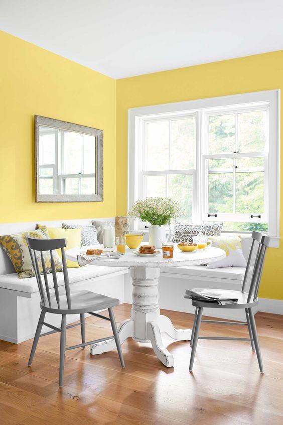 un coin repas coloré avec des murs jaunes, un siège d'angle blanc, une table blanche, des chaises grises et des oreillers gris et jaunes