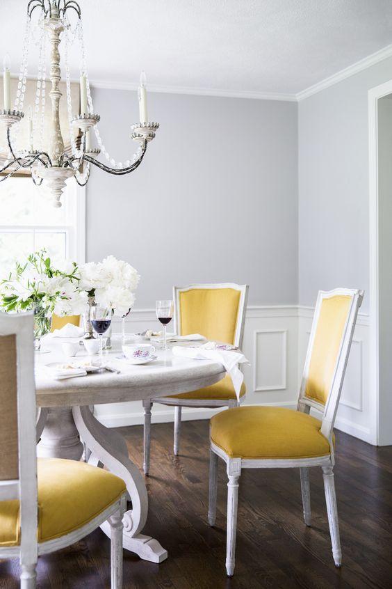 une salle à manger classique raffinée avec des murs gris, des boiseries, une grande table blanche, des chaises jaunes, un beau lustre en cristal et des fleurs blanches