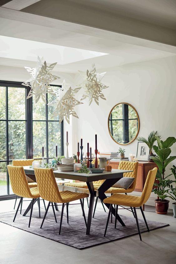 une salle à manger jolie et fantaisiste avec une table à tréteaux grise, des chaises jaunes, des oreillers, des étoiles en papier sur la table et des bougies