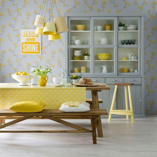 une jolie et mignonne salle à manger grise et jaune avec du papier peint à fleurs, un buffet gris, un ensemble de salle à manger en bois, des suspensions et des textiles jaunes