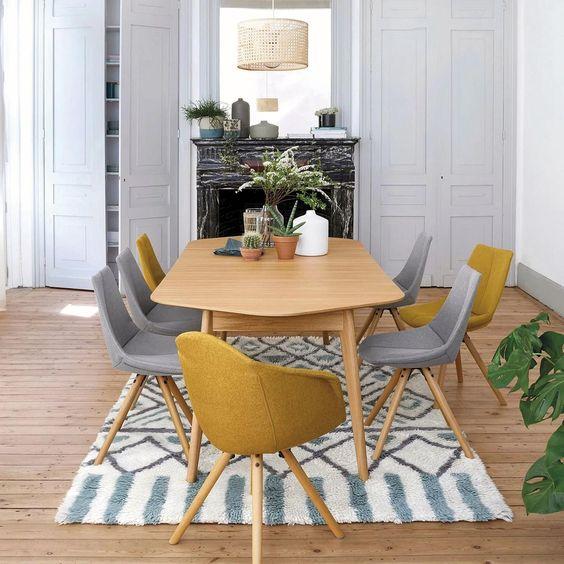 un petit espace salle à manger moderne et confortable avec des éléments de rangement gris, une cheminée en marbre noir, une chaise en bois, des chaises grises et jaunes et des plantes en pot