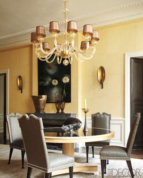 une salle à manger grise et jaune raffinée et chic avec des murs lambrissés jaunes, une table ronde, des chaises grye, un lustre chic et une cheminée en marbre