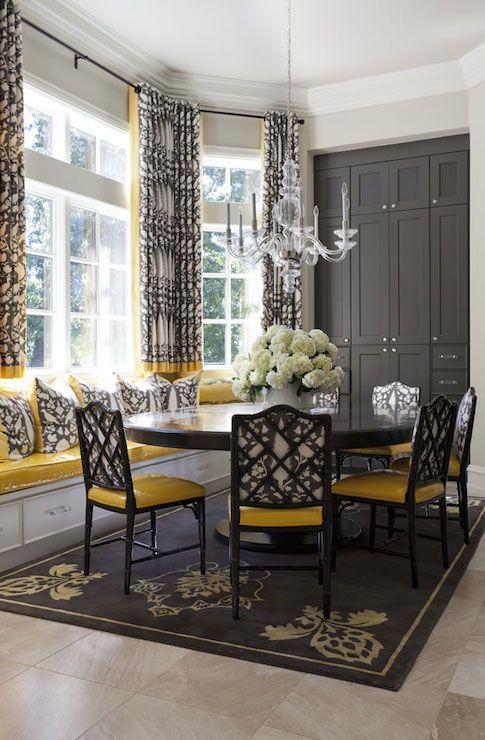 une salle à manger vintage et raffinée avec une baie vitrée, un siège de rebord de fenêtre, une table ronde, des chaises noires et jaunes, un meuble de rangement gris graphite