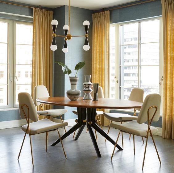 une salle à manger grise et jaune raffinée et élégante avec des murs gris, des rideaux jaunes, une table ronde, des chaises neutres et un joli lustre