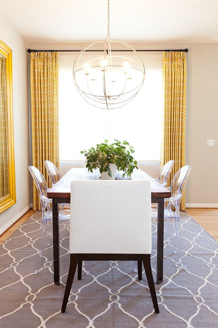 une salle à manger éclectique et chic avec une table en bois, des chaises en acrylique et rembourrées, une suspension sphérique, des rideaux jaunes et un grand miroir