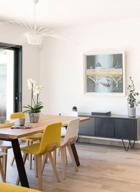 une salle à manger moderne et aérée avec un meuble de rangement gris, une table à manger, des chaises jaunes et blanches et un joli lustre rétro