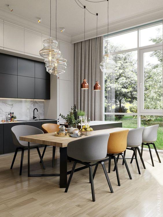 une salle à manger élégante avec une table en bois, des chaises grises et jaunes, des suspensions en verre et en cuivre est très chic
