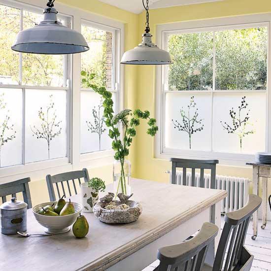 un espace repas vintage aux murs jaunes, une table blanche, des chaises et des suspensions grises, une console en bois