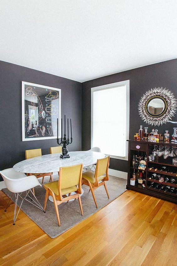 une élégante salle à manger grise et jaune avec des murs gris graphite, une table ovale en marbre, des chaises jaunes, un bar sombre et un miroir sunburst