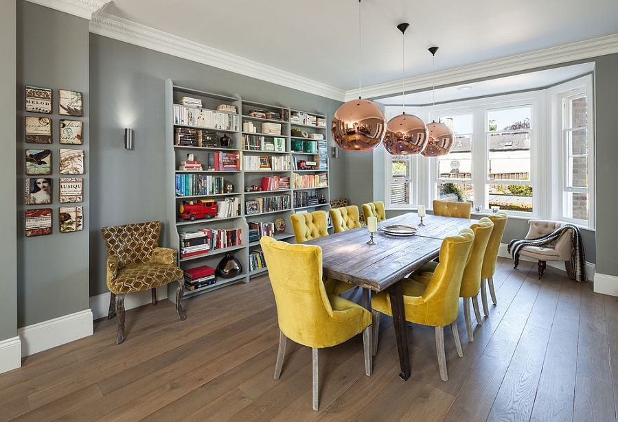 une salle à manger accueillante avec une baie vitrée, des murs gris, une table en bois, des chaises jaunes, des suspensions en cuivre et un meuble de rangement mural