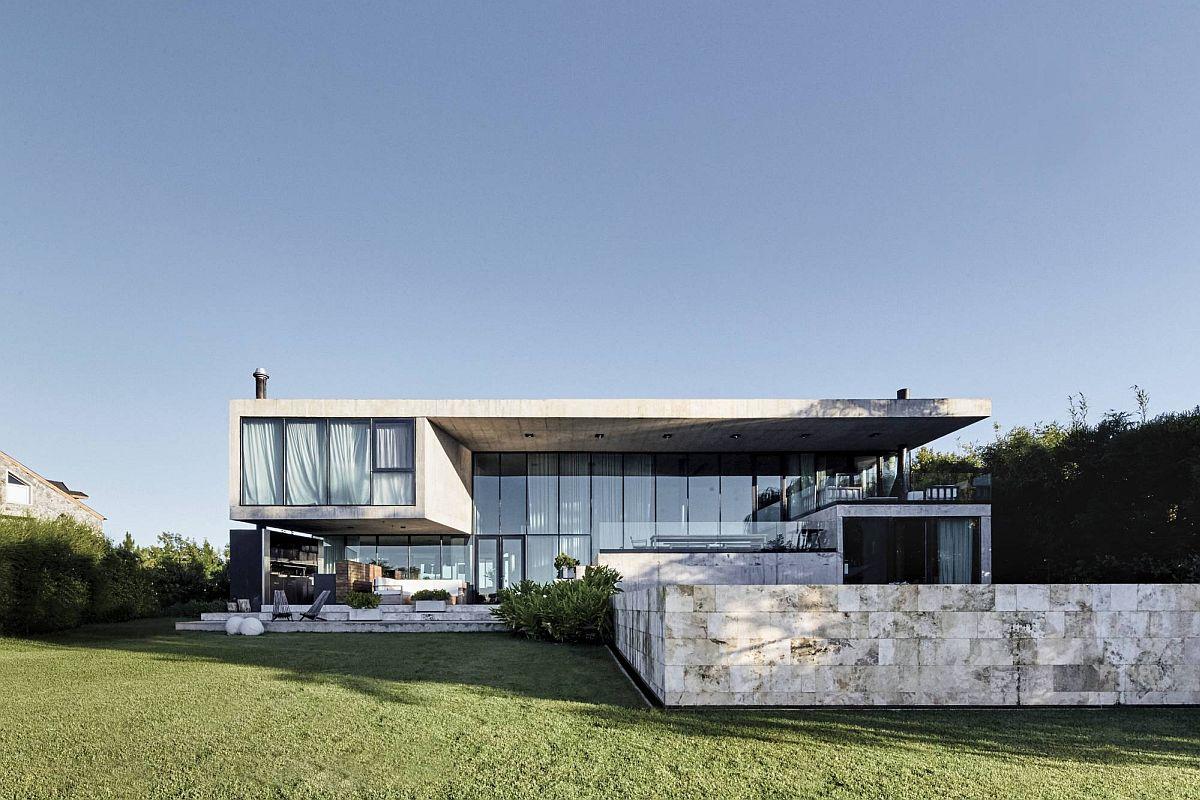 Façade arrière contemporaine de la maison moderne de Buenos Aires avec un grand coin salon extérieur et une piscine