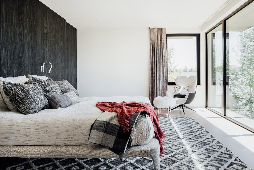 La chambre présente un mur d'accent en bois, un mobilier et une décoration gris et blanc et un accès à la terrasse
