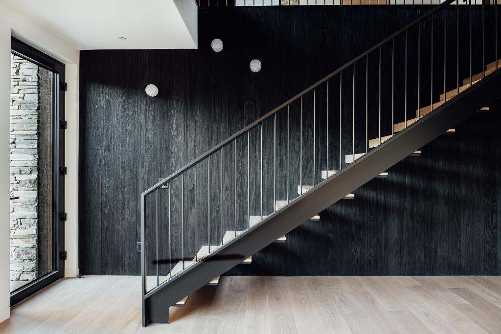 Un accoya teinté sombre tapisse le mur derrière l'escalier