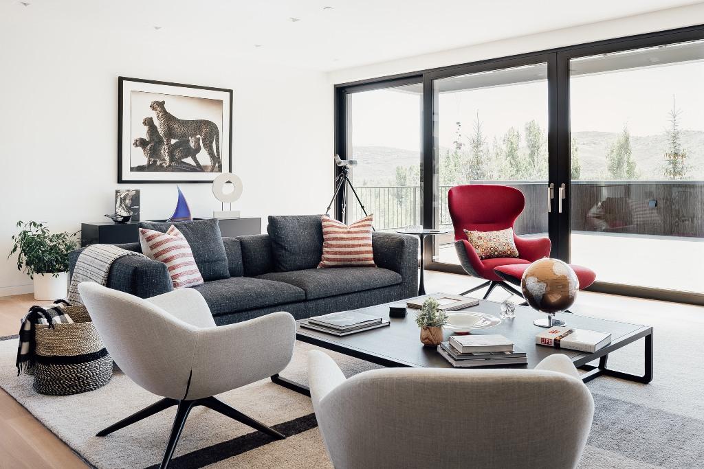 Le salon est fait avec des meubles gris, une chaise rouge audacieuse, des plantes en pot et est ouvert sur la terrasse
