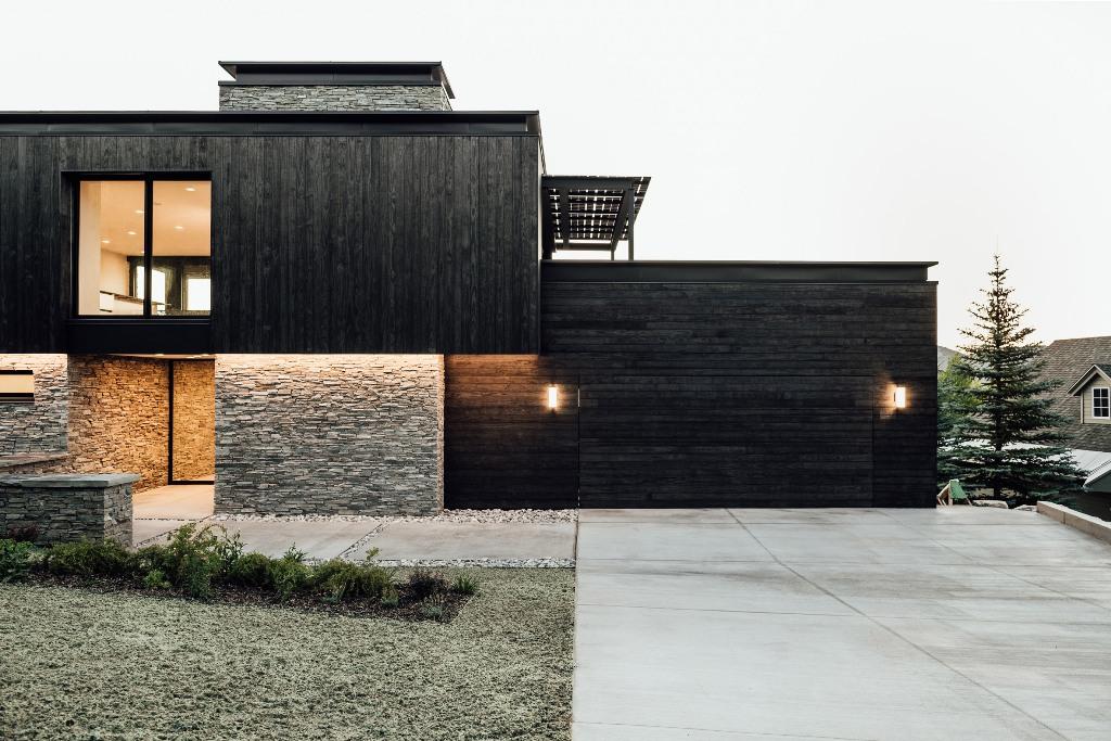 L'extérieur de la maison est fait de bois noirci et de pierre pour la relier à l'environnement