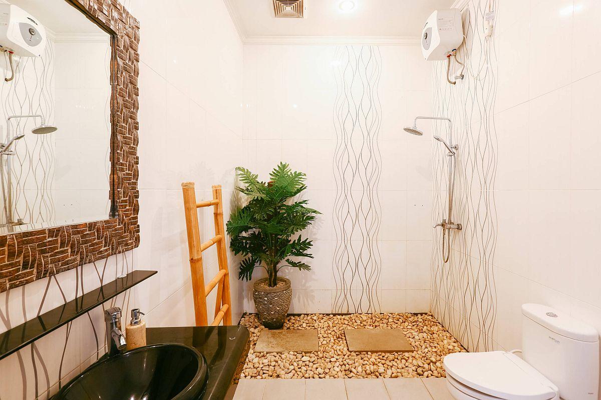 Des galets, un soupçon de verdure et des finitions naturelles apportent un style tropical à la salle de bain neutre