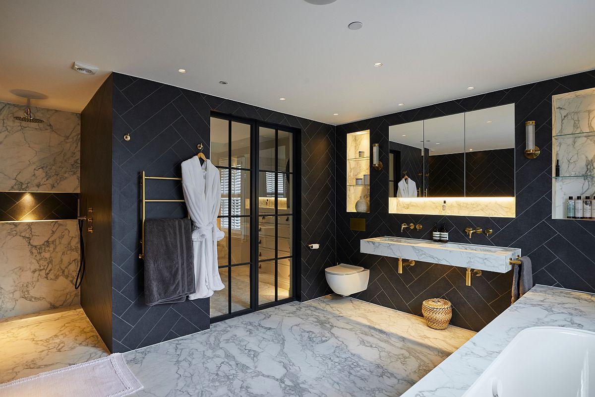 Les finitions sombres et les luminaires en laiton contrastent avec les surfaces en marbre poli de la salle de bain