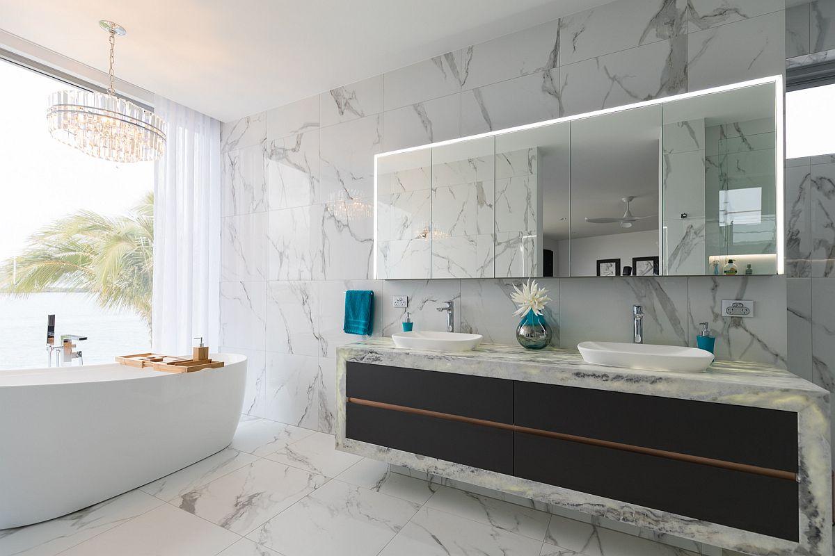 Un meuble-lavabo contemporain élégant et élégant en noir contraste avec le fond en marbre blanc