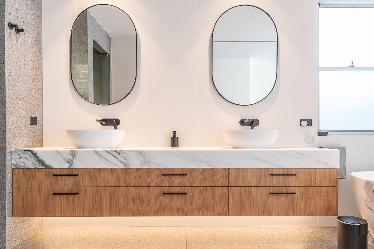 Ajoutez un comptoir en marbre au meuble-lavabo flottant en bois dans la salle de bain contemporaine