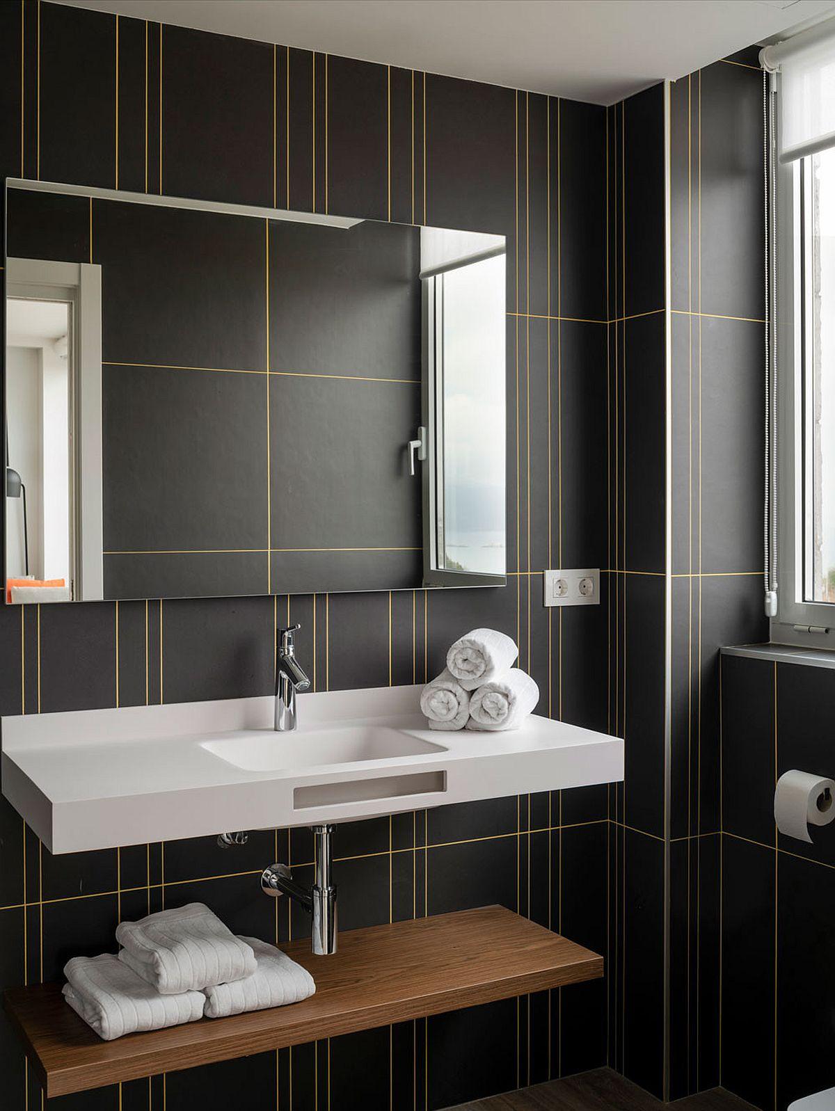 L'utilisation fringante de lignes jaunes d'une manière minimaliste vole la vedette dans cette salle de bain gris foncé