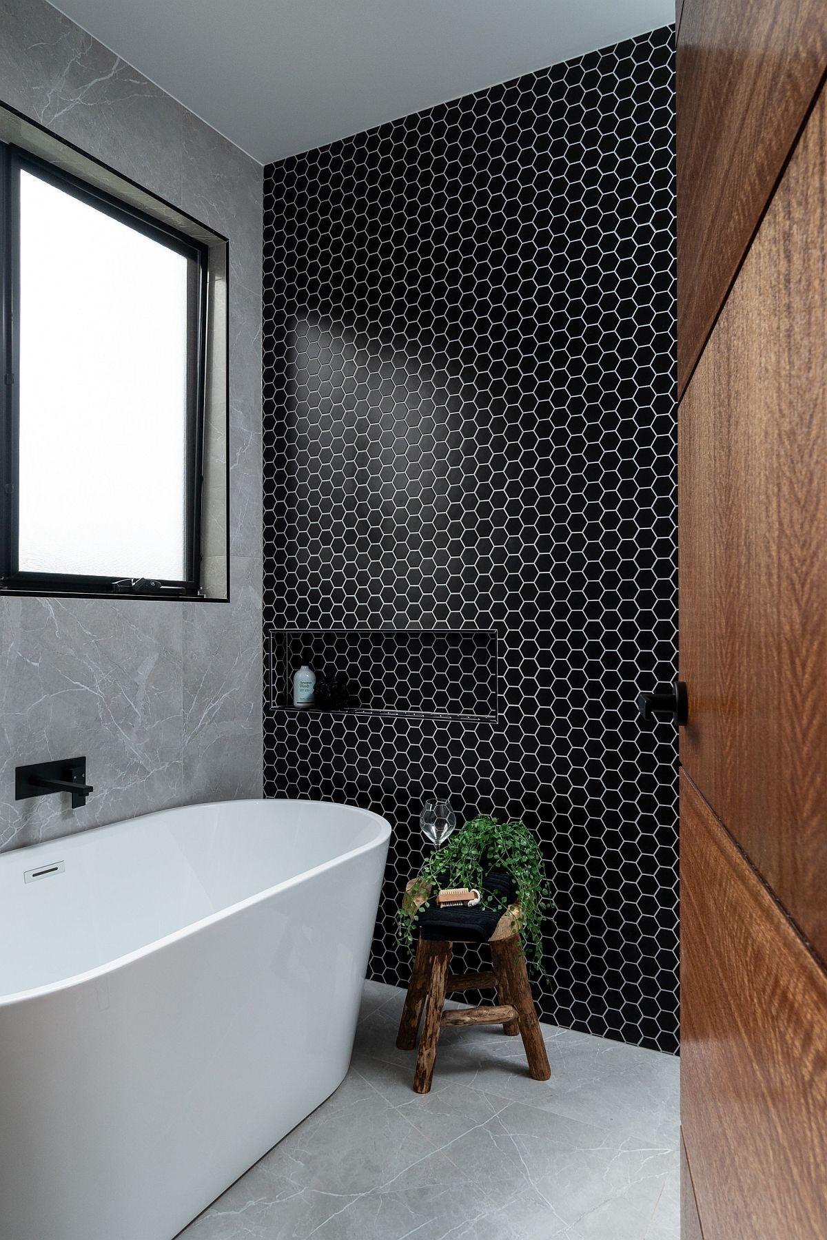 De petits carreaux hexagonaux noirs volent la vedette dans cette salle de bain moderne aux teintes neutres