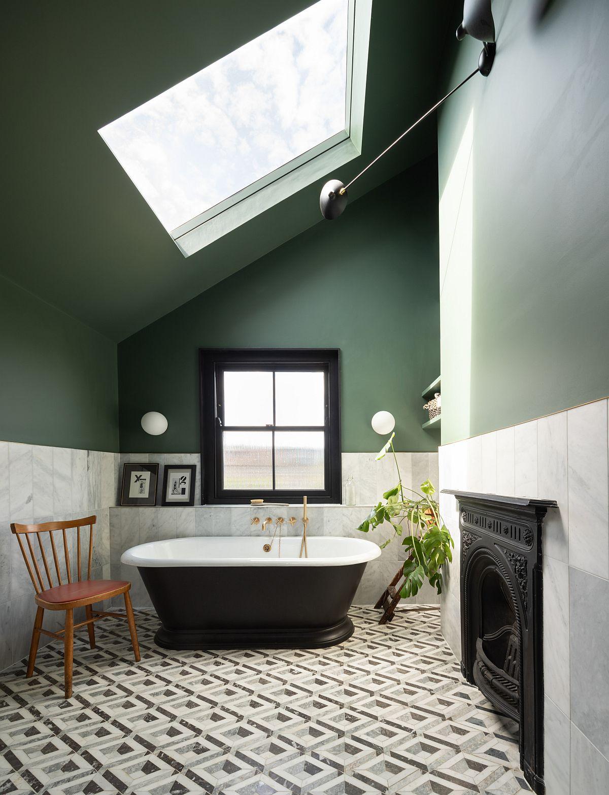 Le bain traditionnel apporte un point focal noir à cette salle de bain éclectique en vert et blanc