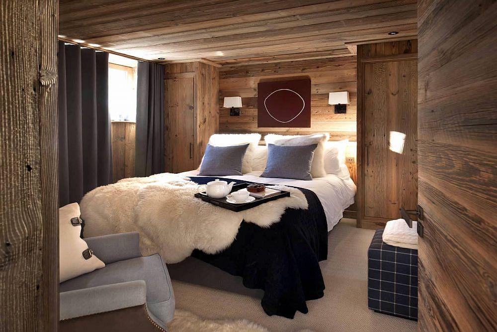 Les rideaux et les couleurs d'oreillers apportent un gris bleuâtre foncé à la chambre de style chalet boisé