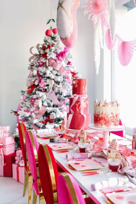un espace de Noël lumineux décoré en rouge, rose et or, avec des éventails en papier, des rubans et des ornements est une idée audacieuse