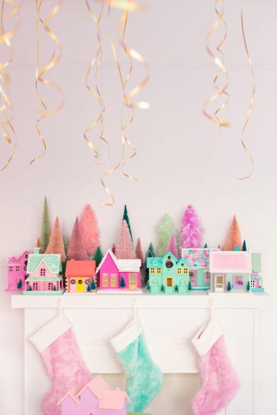 une cheminée de Noël lumineuse et amusante avec des bas roses et verts, des maisons roses et vertes et de petits guirlandes pour une touche amusante