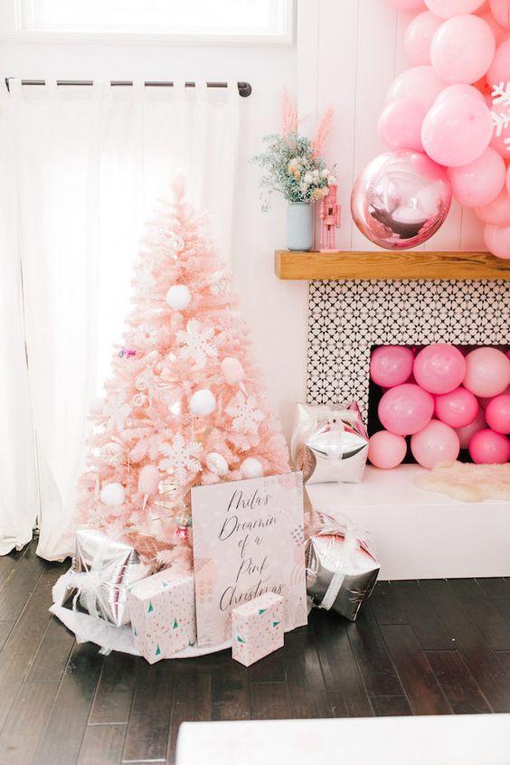 un arbre de Noël blush avec des ornements blancs, des coffrets cadeaux imprimés, des ballons roses dans la cheminée et au-dessus