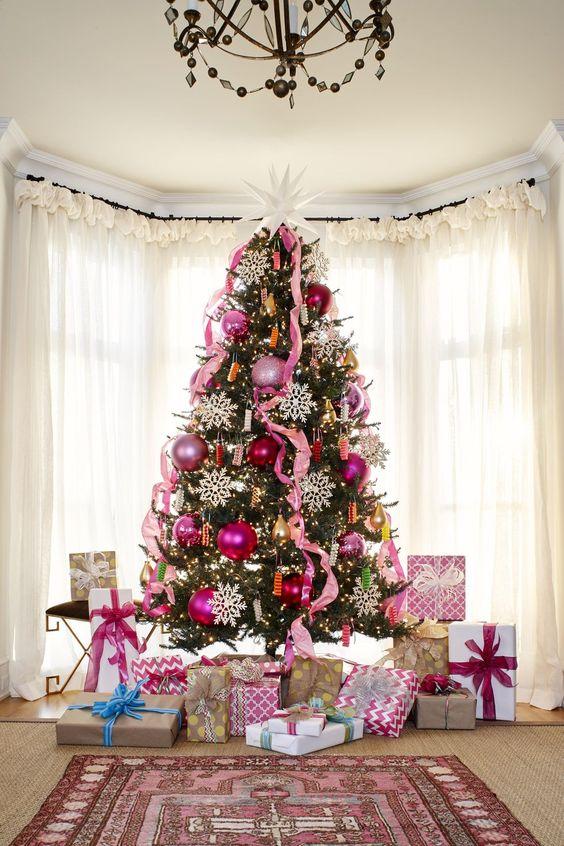un arbre de Noël audacieux décoré avec des ornements de paillettes roses et roses, des rubans roses, des lumières et de grands flocons de neige et une grande étoile sur le dessus