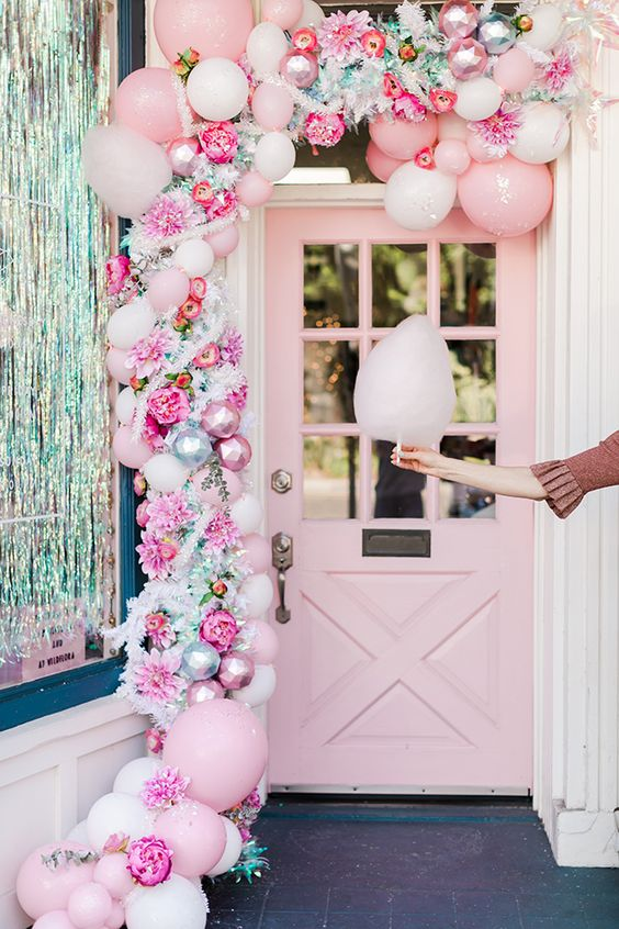 une jolie guirlande de Noël rose de ballons, d'ornements roses, de fausses fleurs et de verdure est une belle idée