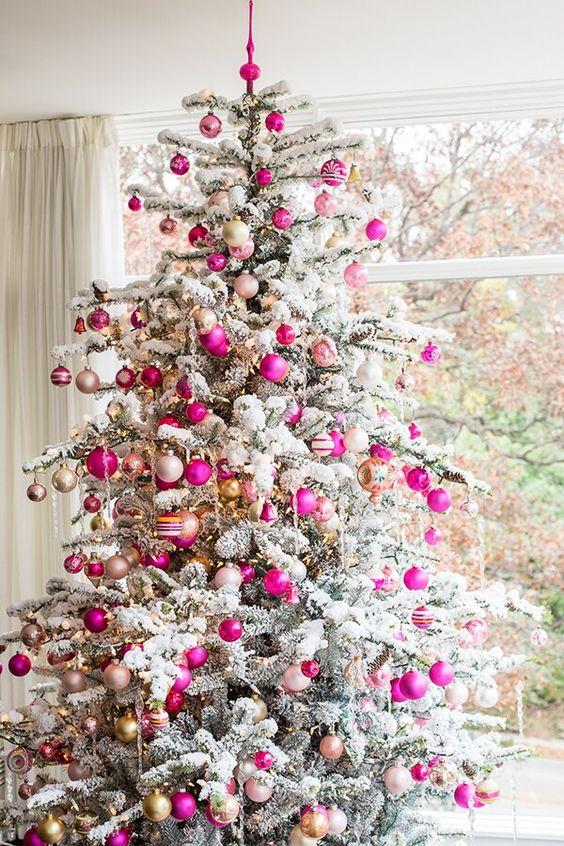 un arbre de Noël floqué décoré d'ornements et de lumières neutres, rose vif et fard à joues semble glamour, chic et très moderne