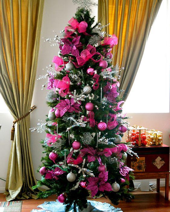 un arbre de Noël glamour avec des ornements rose vif et fuchsia et des fleurs en tissu, des brindilles d'argent, des perles et des lumières est une idée brillante