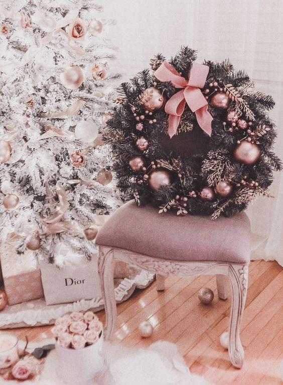 une guirlande de Noël sapin raffinée et glamour parsemée d'ornements roses et d'un grand noeud est une idée chic pour apporter une touche de glamour