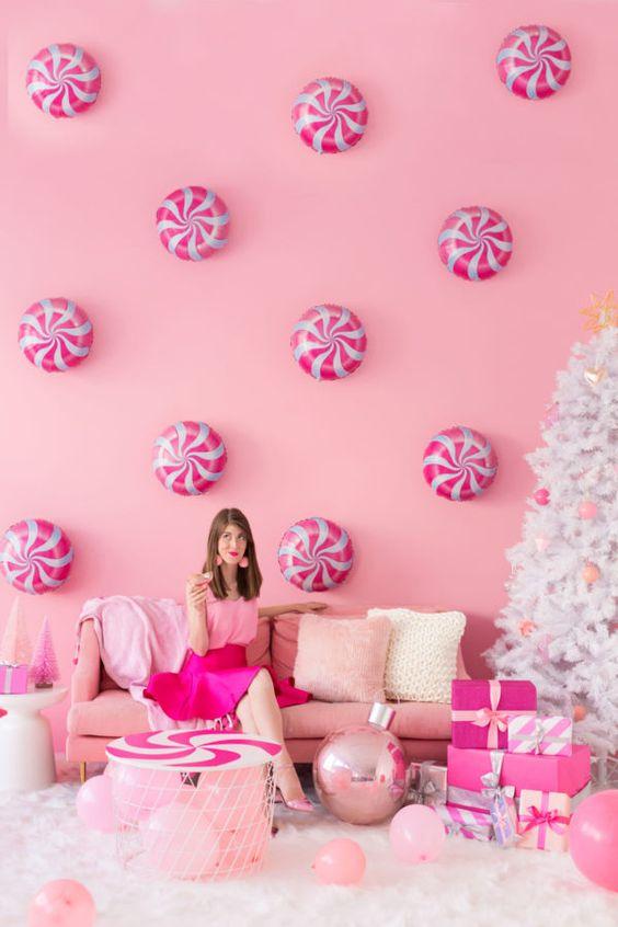un espace de vacances rose avec des menthe poivrée sur le mur, des meubles roses et des ballons et des ornements roses sur un arbre de Noël blanc