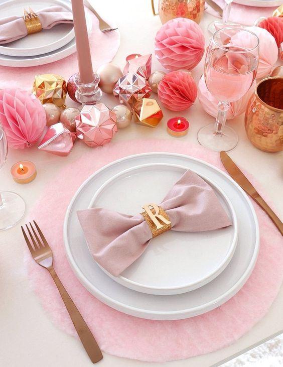 une table de vacances rose avec des chargeurs roses, des ornements, des pompons en papier, des verres, des bougies et des serviettes ainsi que des couverts mates