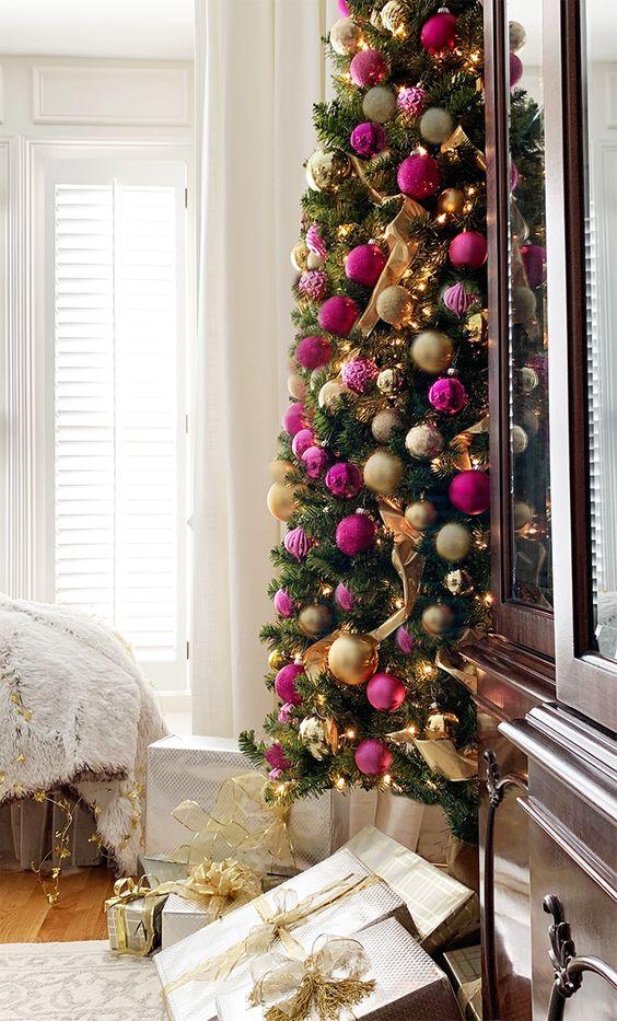 un sapin de Noël raffiné avec des lumières, des ornements et des rubans or et rose vif et fuchsia est une idée magnifique pour un espace de vacances chic