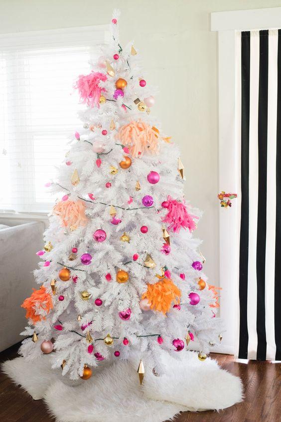 un arbre de Noël blanc avec des ornements rose vif, fuchsia, or et orange et des pompons lumineux est tout au sujet de la décoration moderne et des couleurs vives