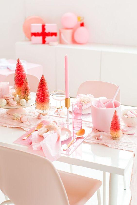 un décor de table de Noël rose simple et moderne avec des draps rose clair, des bougies, des chargeurs en acrylique, des ornements et des arbres de guirlandes ombrées