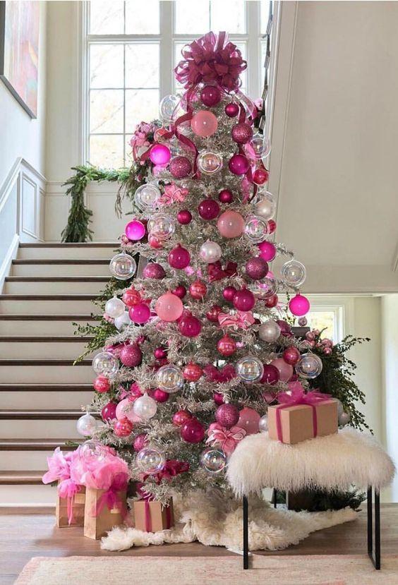 un sapin de Noël en argent décoré d'ornements roses, fuchsia, transparents et argentés et un grand nœud fuchsia sur le dessus