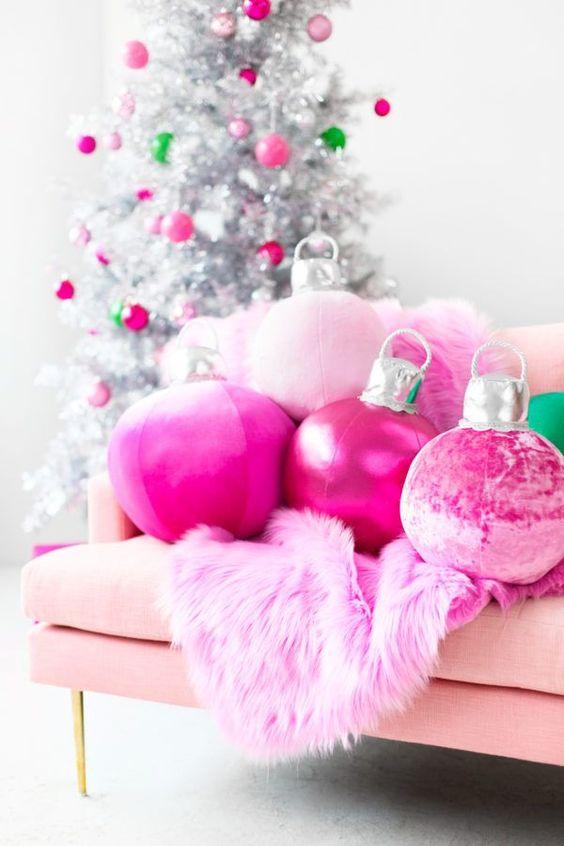 oreillers d'ornement de Noël rose vif et une couverture en fausse fourrure ainsi que des ornements assortis sur l'arbre de Noël argenté