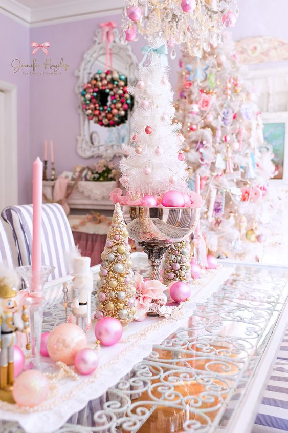 décoration de Noël glamour avec des ornements et des bougies pêche et rose vif, des perles, des ornements roses dans un bol et un mini arbre blanc avec des ornements blush et roses