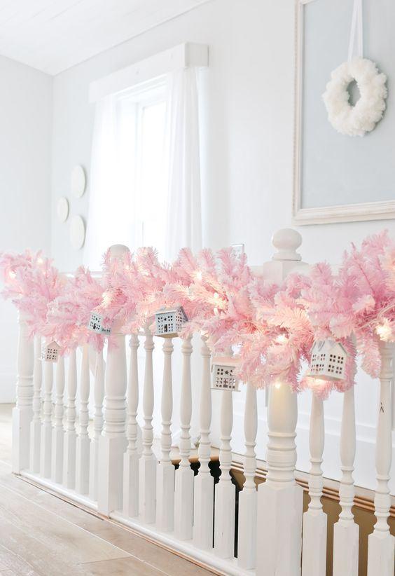 belle décoration de balustrade de vacances avec une guirlande de branches de sapin rose, des lumières et des mini maisons suspendues est une belle idée