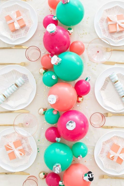 Paysage de table audacieux et amusant avec des ornements verts, roses et fuchsia comme pièce maîtresse, des verres roses, des couverts en or et des assiettes imprimées