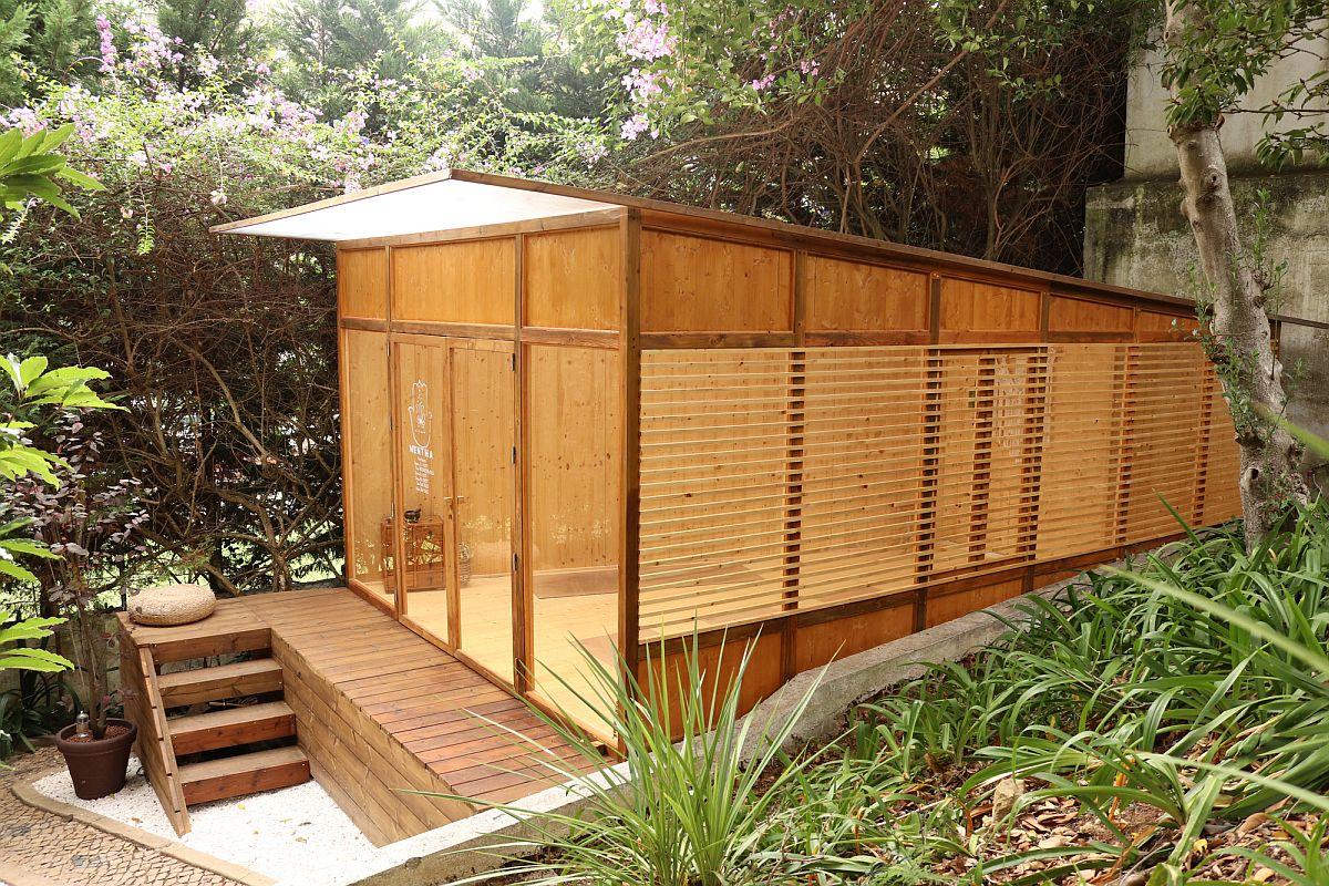 Des panneaux en bois lamellé-croisé façonnent l'extérieur du petit studio de yoga dans la cour