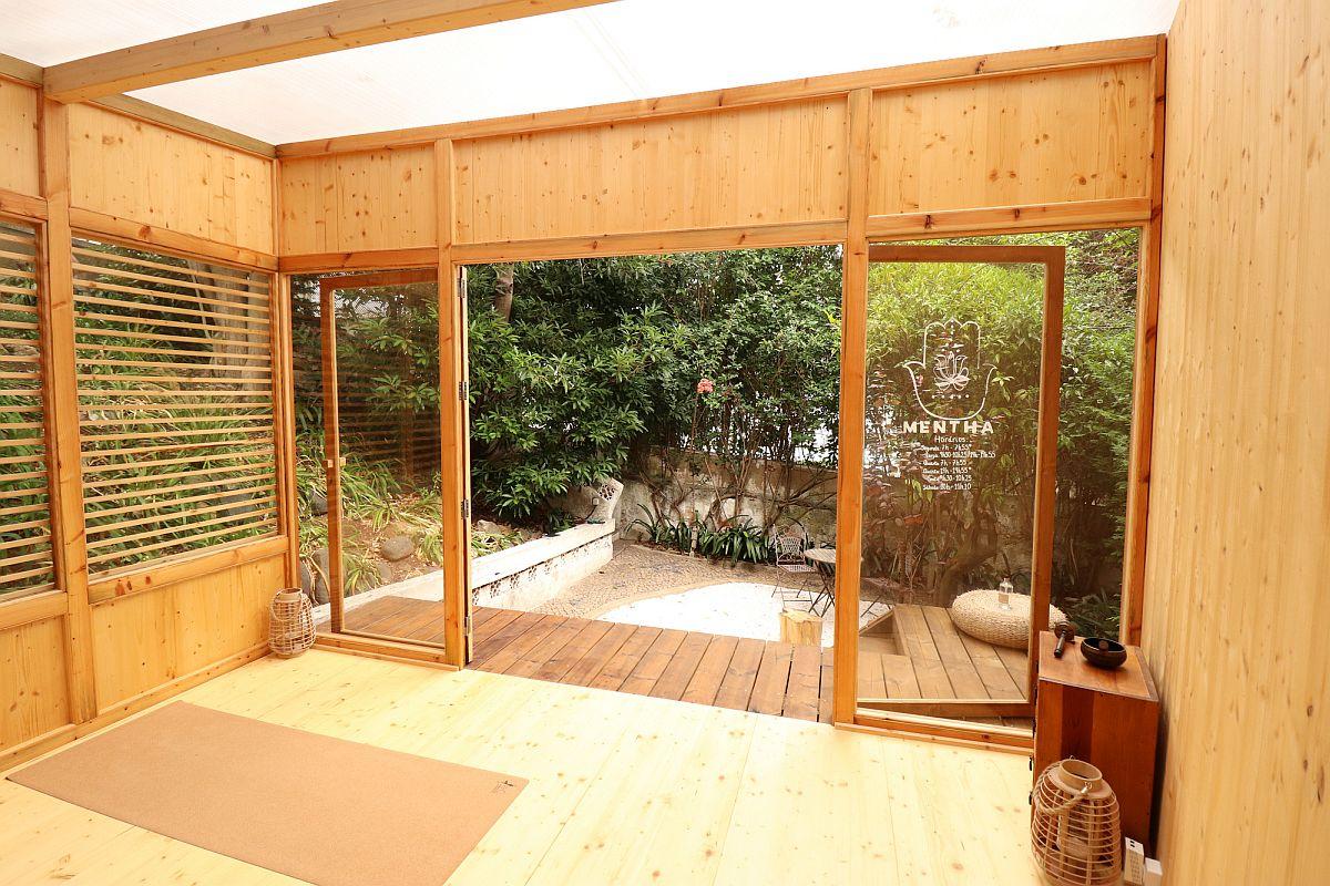 Une petite terrasse en bois à l'extérieur du studio de yoga prolonge magnifiquement l'espace