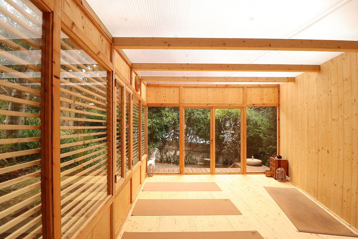 L'utilisation du verre amène le paysage du jardin dans le studio de yoga